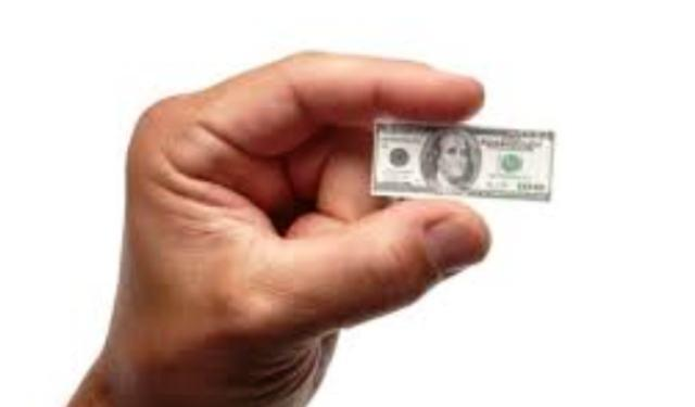 currency devaluation depicted by small dollar large hand